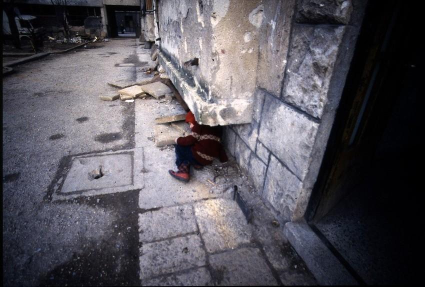 GUILLERMO CERVERA.  Un niño refugiado bajo una estructura de cemento en Mostar en un bombardeo, Bosnia- Herzegovina.