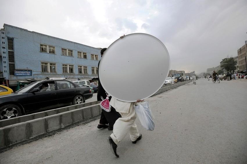 GUILLERMO CERVERA. Un afgano transportando antena parabólica en Kabul, Libia.