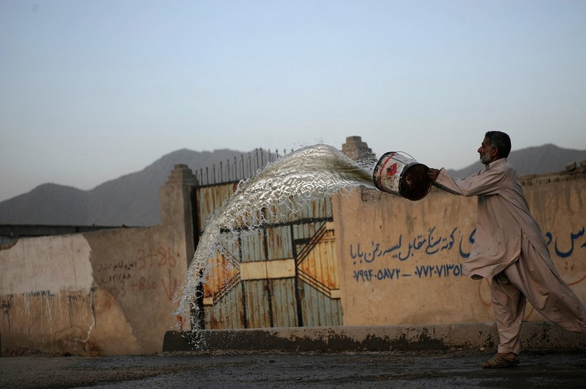GUILLERMO CERVERA. Un afgano de Kabul limpiando la acera frente a su comercio después de un atentado suicida con coche bomba.