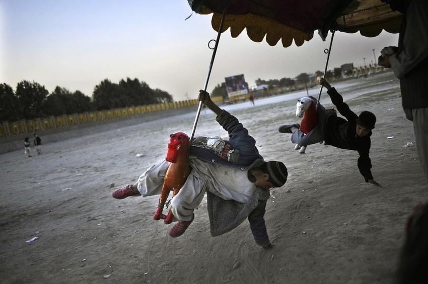 GUILLERMO CERVERA. Niños tayikos dando vueltas en caballos en kabul, Afganistán